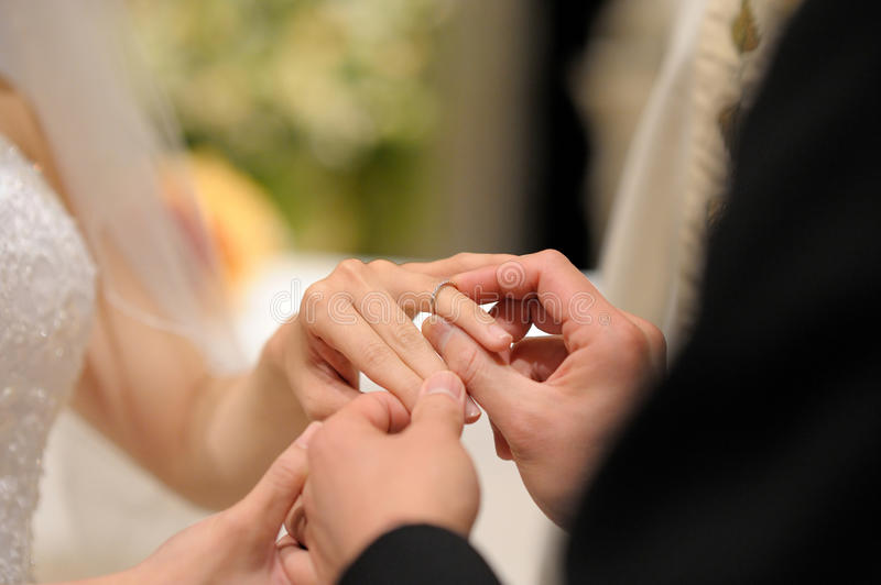 Groom putting a ring on bride's finger royalty free stock image