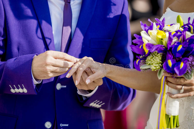 Groom is putting the wedding ring on bride's finger stock photography