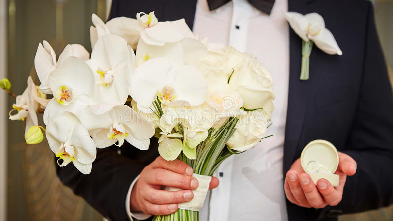 Groom with rings and bouquet. The groom with wedding rings and bouquet royalty free stock images