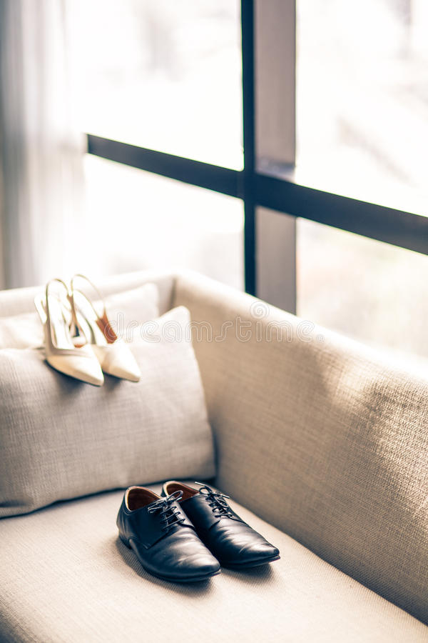 The groom's and Bried shoes against the window. Shoe sofas studio style wedding wedlock white groom's bridal stock photography