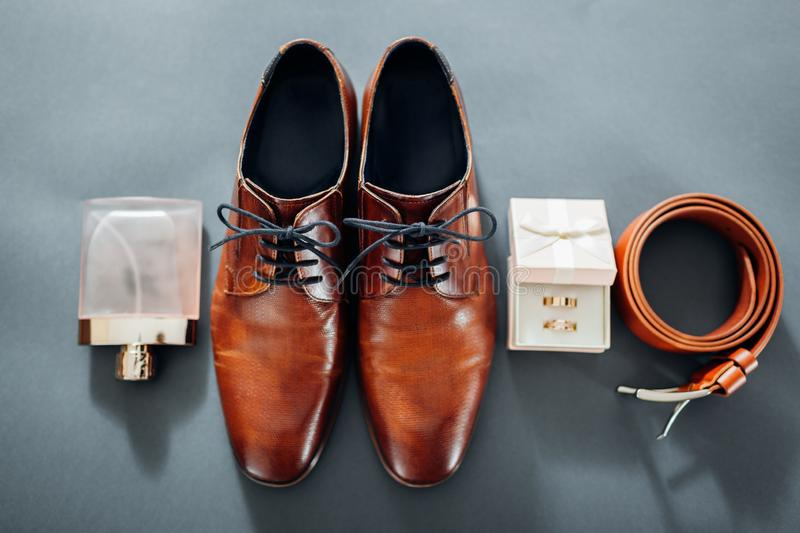 Groom`s wedding day accessories. Brown leather shoes, belt, perfume, golden rings. Male fashion stock photo