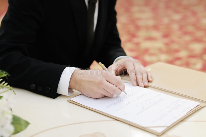 Groom signing marriage license or wedding contract royalty free stock photos