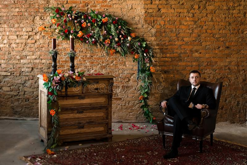 Groom sitting in a big chair confidently royalty free stock photos