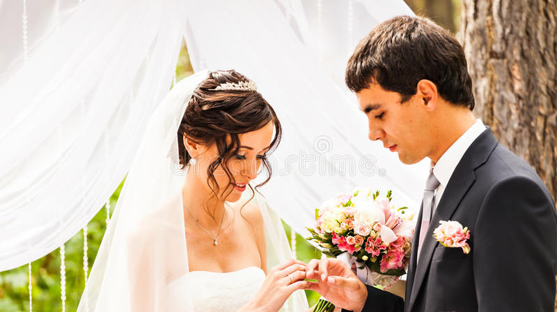 Groom slipping ring on finger of bride at wedding.  stock image
