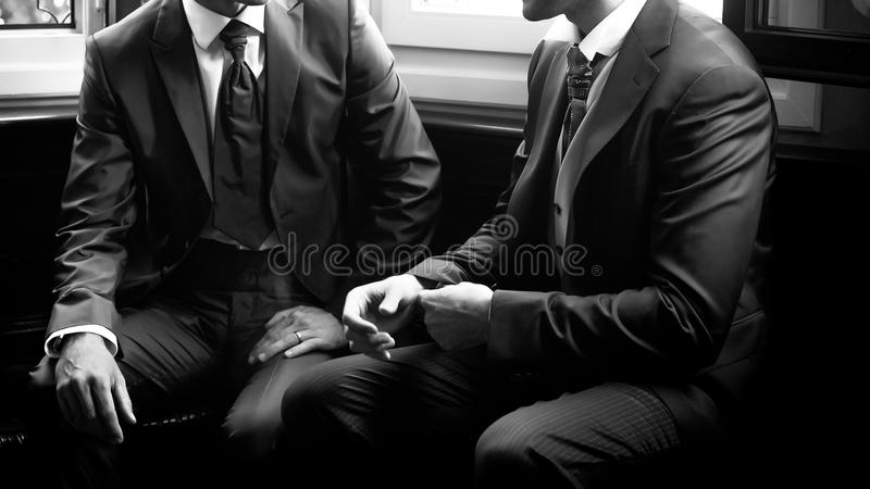 Groom speaks with friend stock photography