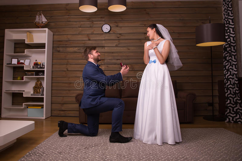 Groom standing on his knees against happy bride stock photos