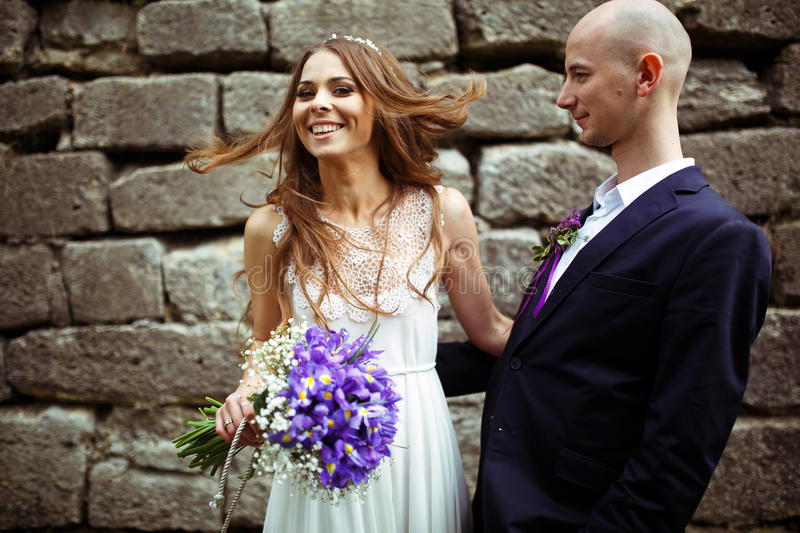 Groom stands behind a smiling bride stock photos