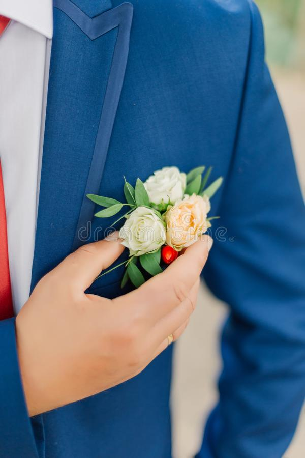 The groom straightens the boutonniere of flowers on his jacket. The groom straightens the boutonniere of flowers on his jacket royalty free stock photos