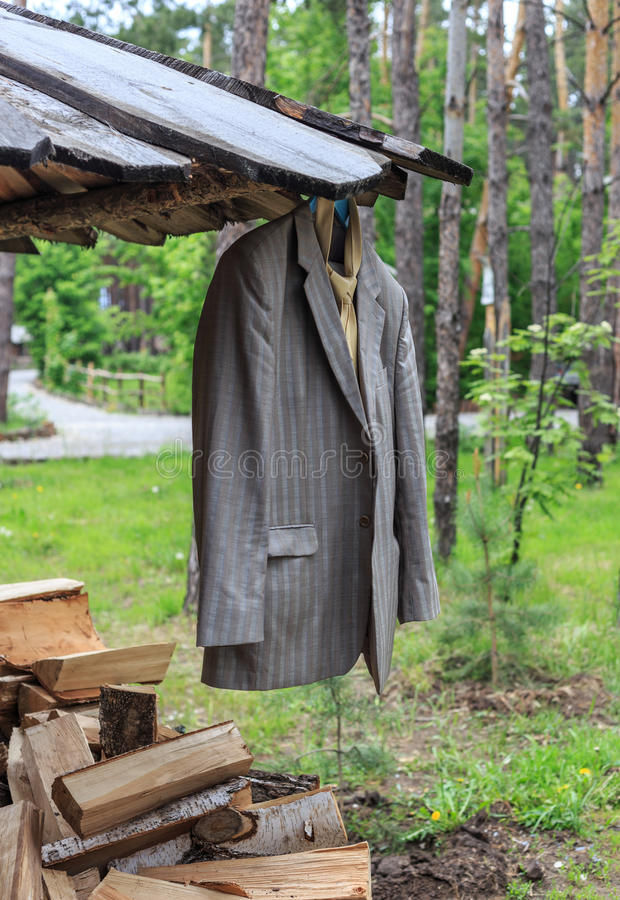 Groom suit hanging on roof of rustic wood racks outdoors. Grey groom suit hanging on roof of rustic wood racks outdoors stock photography