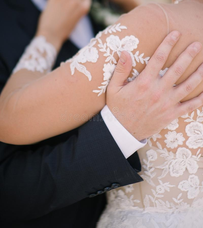 The groom in a suit hugs the bride in a wedding dress stock images