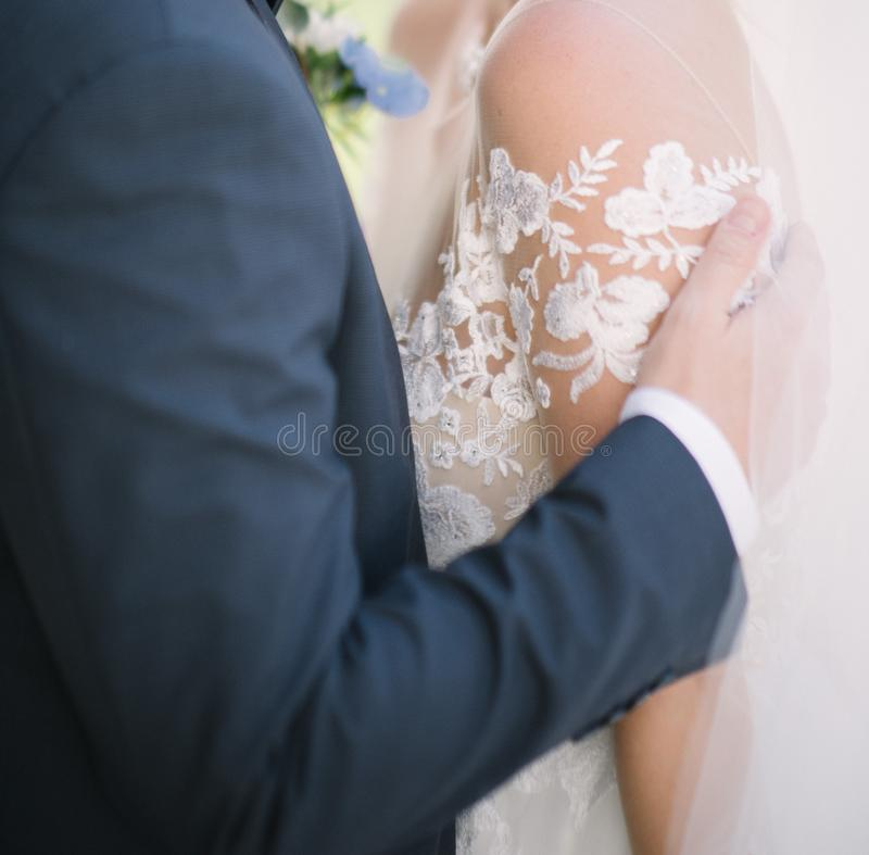 The groom in a suit hugs the bride in a wedding dress royalty free stock photo