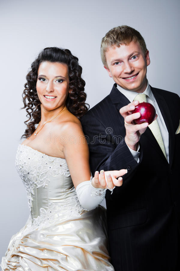 Groom taking red apple from beautiful bride stock photo