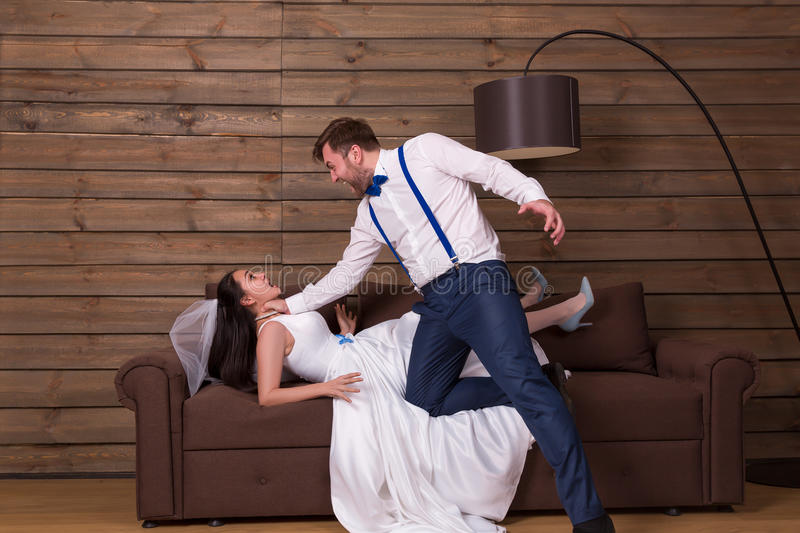 Groom trying to choke bride in white dress stock images
