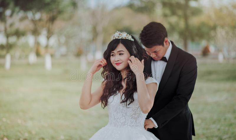 Groom Tying Bride's White Lace Wedding Gown at the Back royalty free stock photo