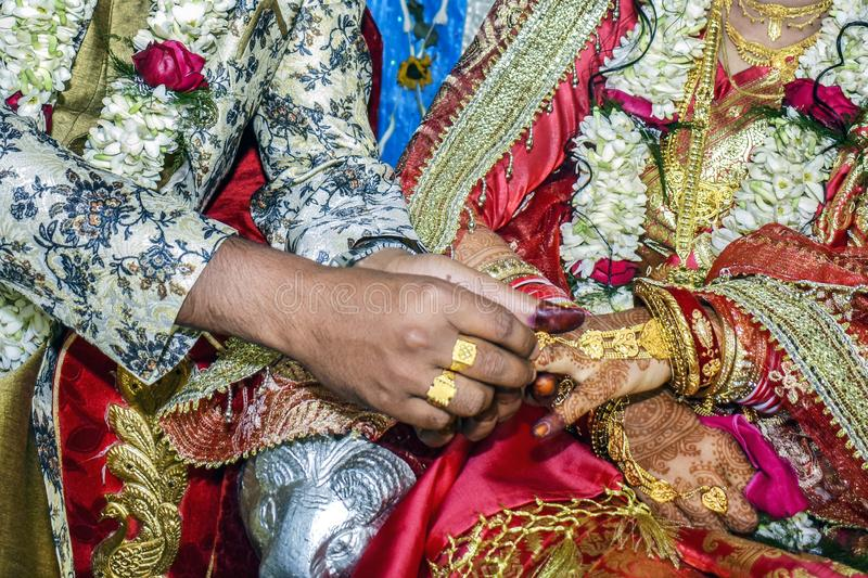 The groom wearing the bride a wedding ring on her finger stock images