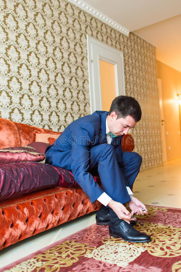 Groom is wearing shoes indoors. Male portrait of handsome guy. Beautiful model boy in colorful wedding clothes. Man is posing stock images