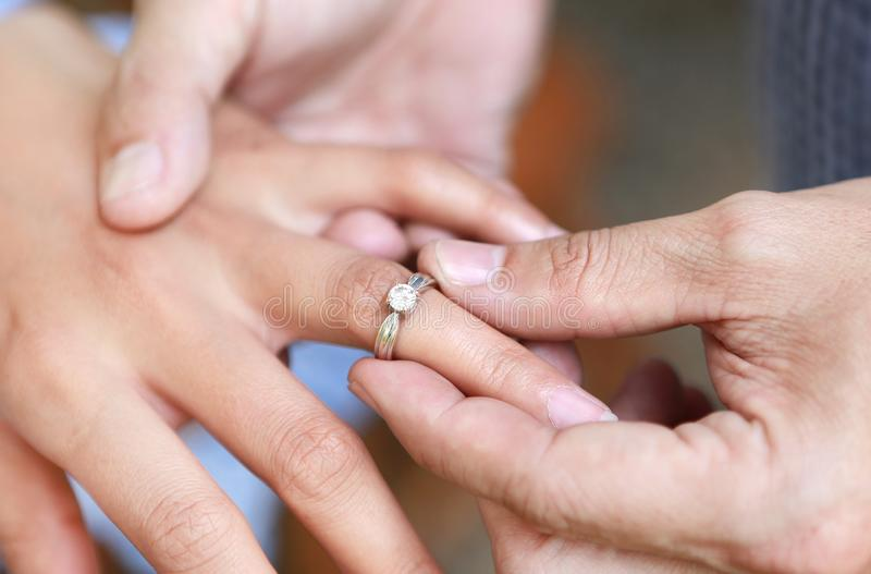 Groom wears ring on bride`s finger. Selective focus at wedding ring.  royalty free stock image