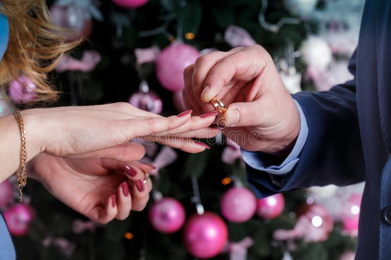The groom wears the ring to bride`s finger at wedding day. Love, happy marry concept. stock photos
