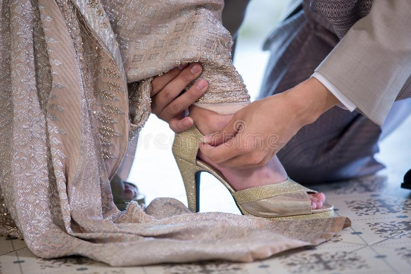 the groom wears wedding shoes on the bride. Young husband helping bride to wear dress sandals stock photo