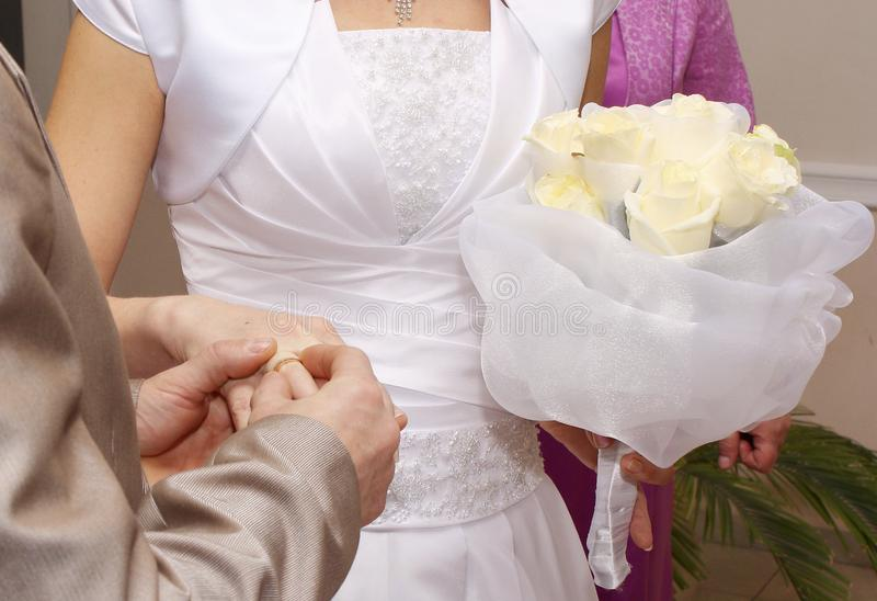 The groom in a wedding suit puts a wedding ring on the bride. She holds a wedding bouquet in another hand.  royalty free stock photos