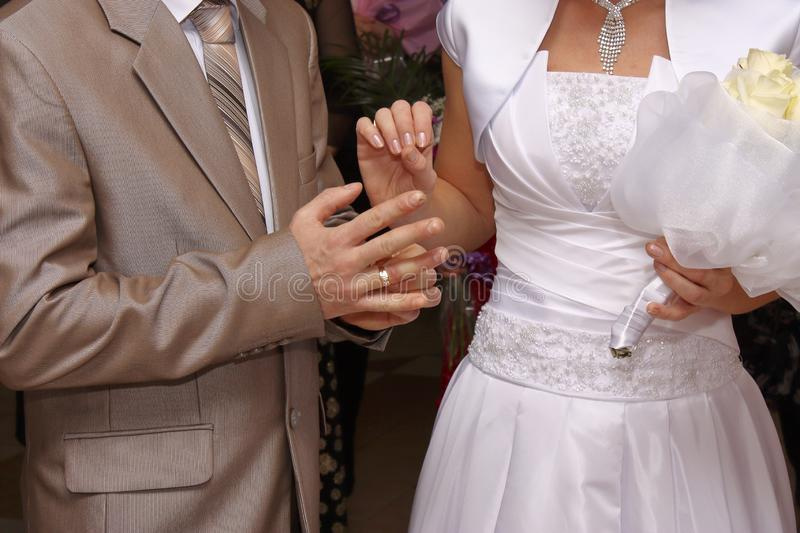 The groom in a wedding suit puts a wedding ring on the bride. She holds a wedding bouquet in another hand.  stock image