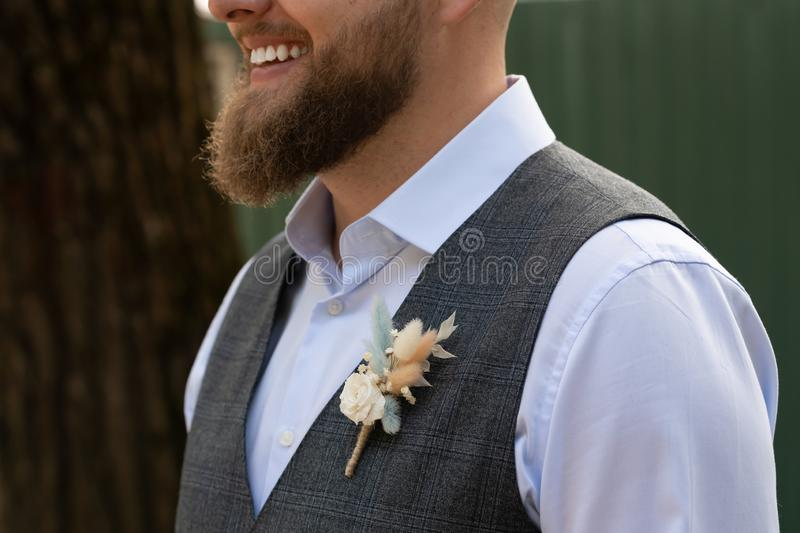The groom in a white shirt, a butterfly and a plaid vest straightens his buttonhole. A young man with a beautiful boutonniere in stock photos