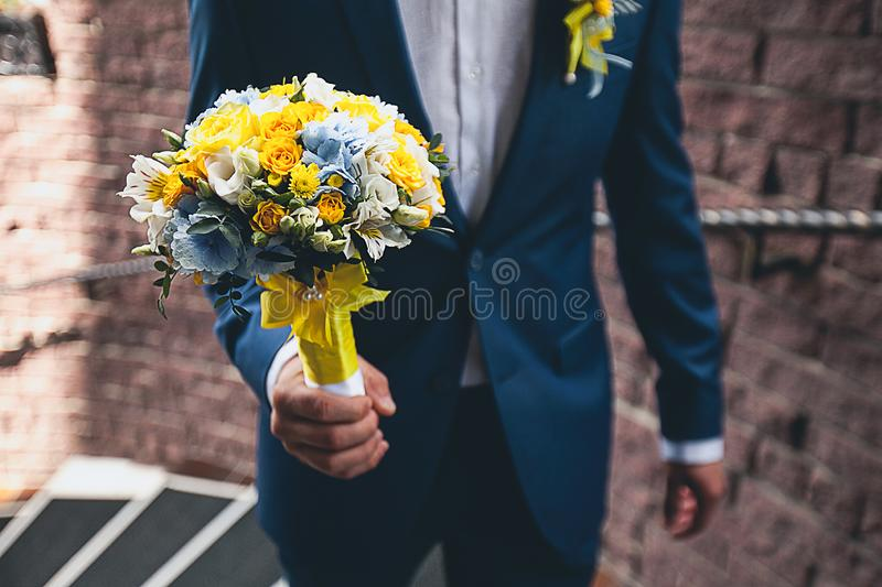 The groom in a white shirt and an elegant blue suit is holding a beautifully decorated bouquet of different flowers and green stock photo
