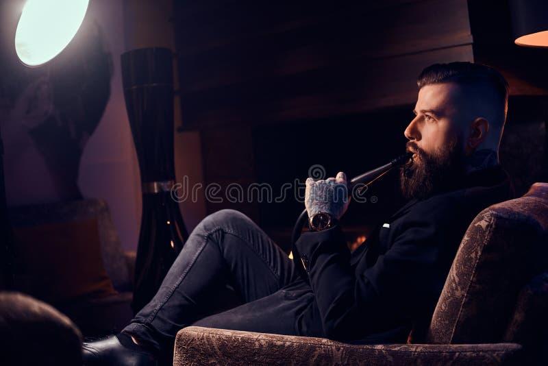 Groomed tattooed o homem está relaxando perto da chaminé na sala escura e no cachimbo de água de fumo fotografia de stock