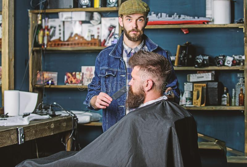 Grooming concept. Barber busy with grooming beard of hipster client, beauty supplies on background. Hipster with beard. Covered with cape serving by royalty free stock photos