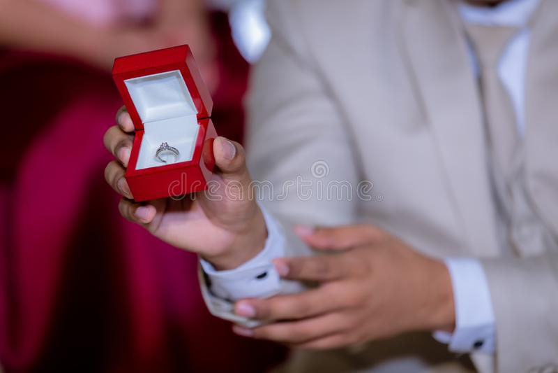 Grooms Hand halten rote Box zu zeigen, Hochzeitsring Hochzeitszeichen und Ehezeichen stockfotografie