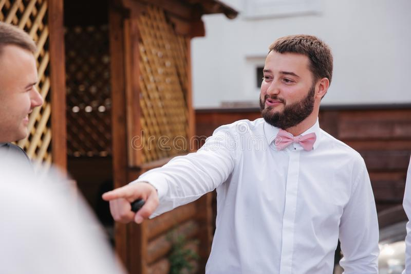 Groomsman ξοδεύει το χρόνο με το νεόνυμφο στο κατώφλι Το γέλιο τύπων και έχει τη διασκέδαση στοκ φωτογραφία