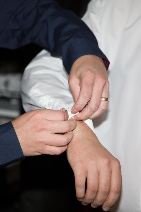 Groomsmen with cufflinks hands helping the groom with buttons for weeding suit. A Groomsmen with cufflinks hands helping the groom with buttons for weeding suit royalty free stock images