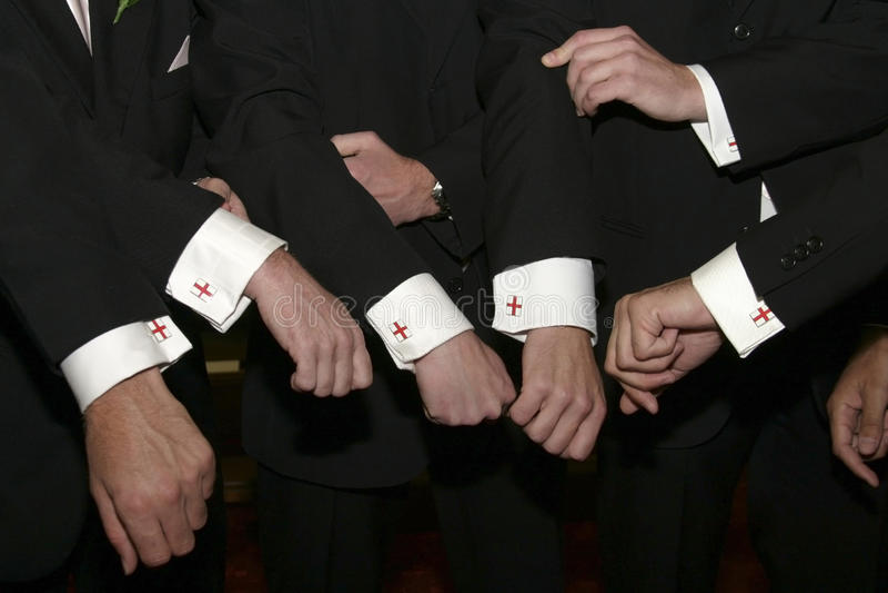 Groomsmen showing their England cufflinks. Groomsmen showing their England cufflinks, flag of Saint George design stock photo