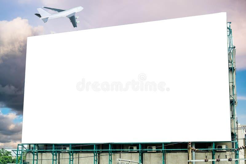 Groot aanplakbord wit spatie en vliegtuig op hemel stock afbeeldingen