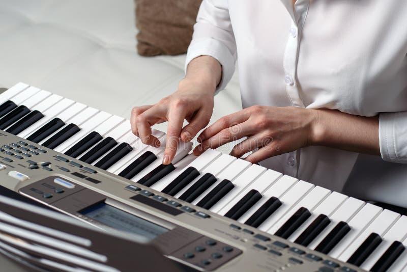 Groot beeld die van vrouwelijke handen de synthesizer spelen stock afbeeldingen