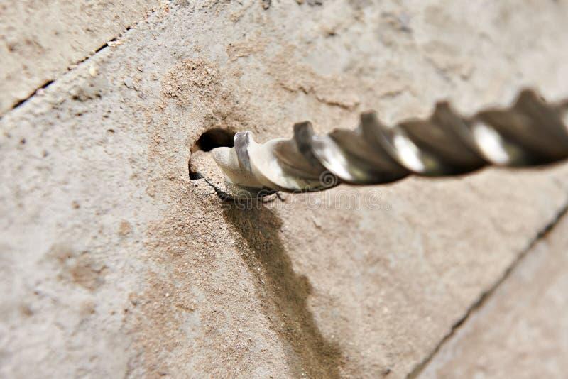 Groot boorbeetje in gat van beton stock foto's