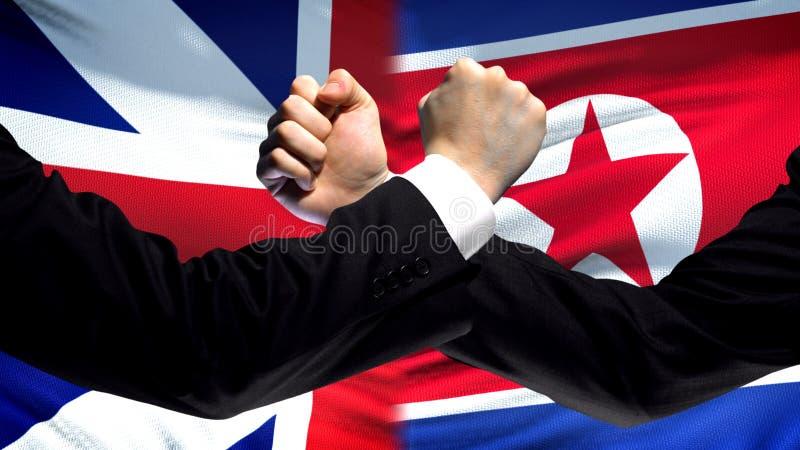 Groot-Brittannië versus de confrontatie van Noord-Korea, vuisten op vlagachtergrond, diplomatie stock fotografie