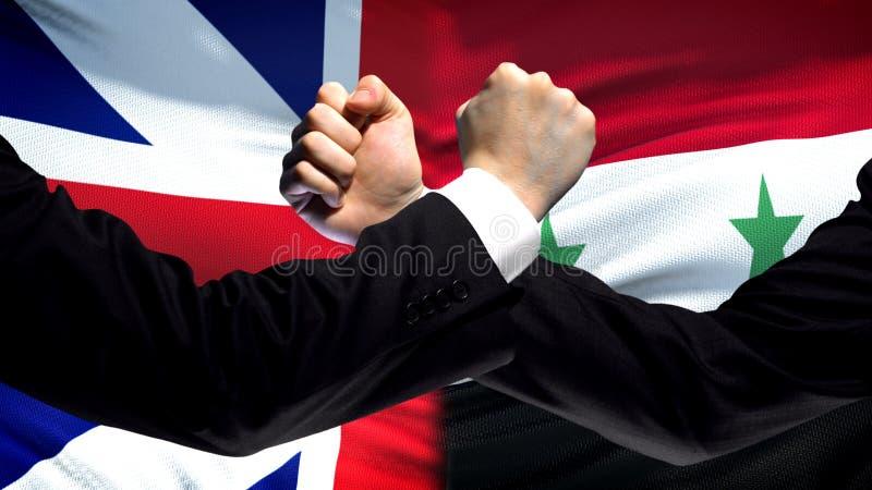 Groot-Brittannië versus de confrontatie van Syrië, vuisten op vlagachtergrond, diplomatie stock afbeeldingen