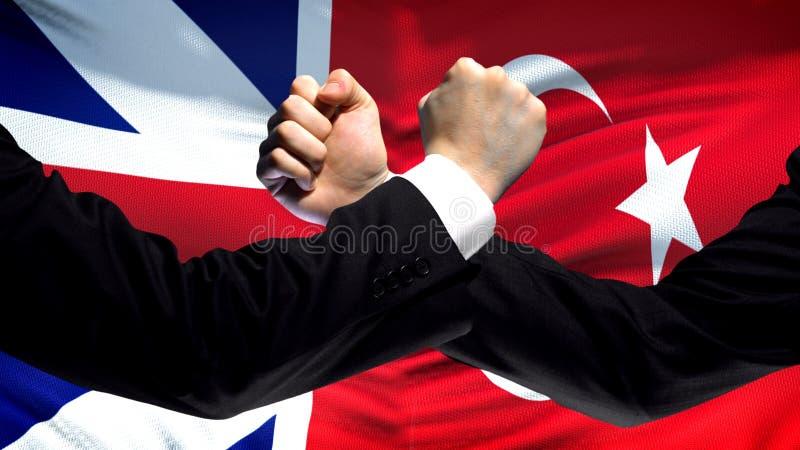 Groot-Brittannië versus de confrontatie van Turkije, vuisten op vlagachtergrond, diplomatie royalty-vrije stock foto