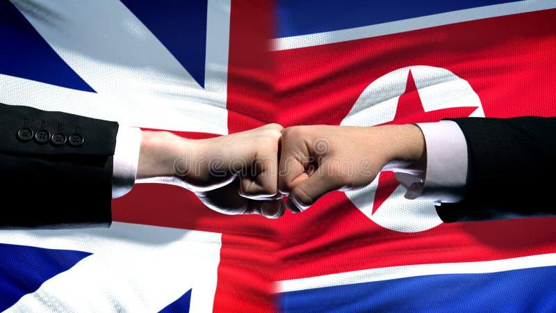Groot-Brittannië versus het conflict van Noord-Korea, vuisten op vlagachtergrond, diplomatie royalty-vrije stock foto's