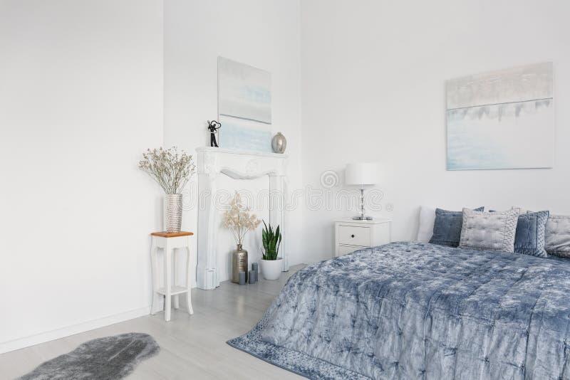 Groot comfortabel bed met elegant blauw beddegoed, witte open haardportaal en bloemen in zilveren vazen, echte foto met exemplaar stock foto