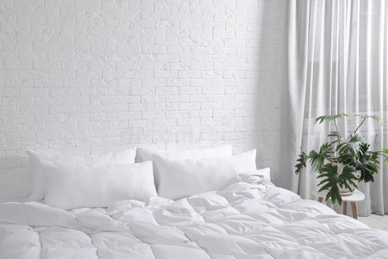 Groot comfortabel bed met hoofdkussens en deken dichtbij witte bakstenen muur binnen stock foto