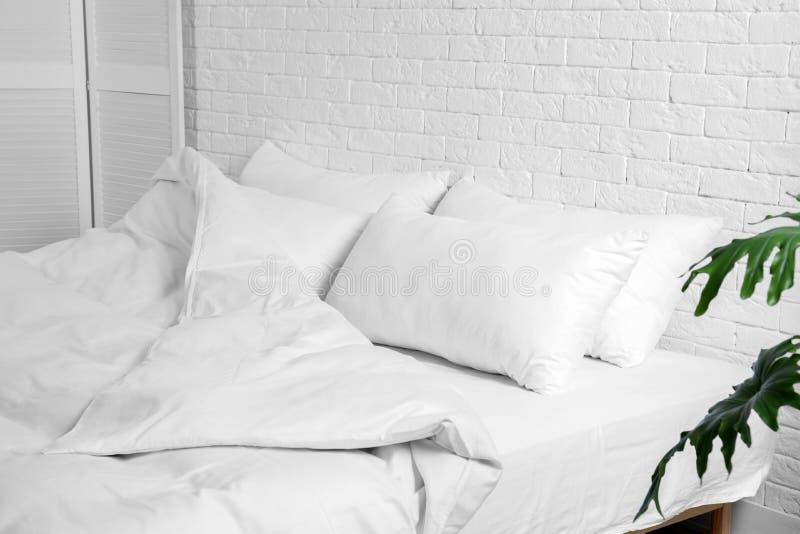 Groot comfortabel bed met hoofdkussens en deken dichtbij witte bakstenen muur binnen stock fotografie