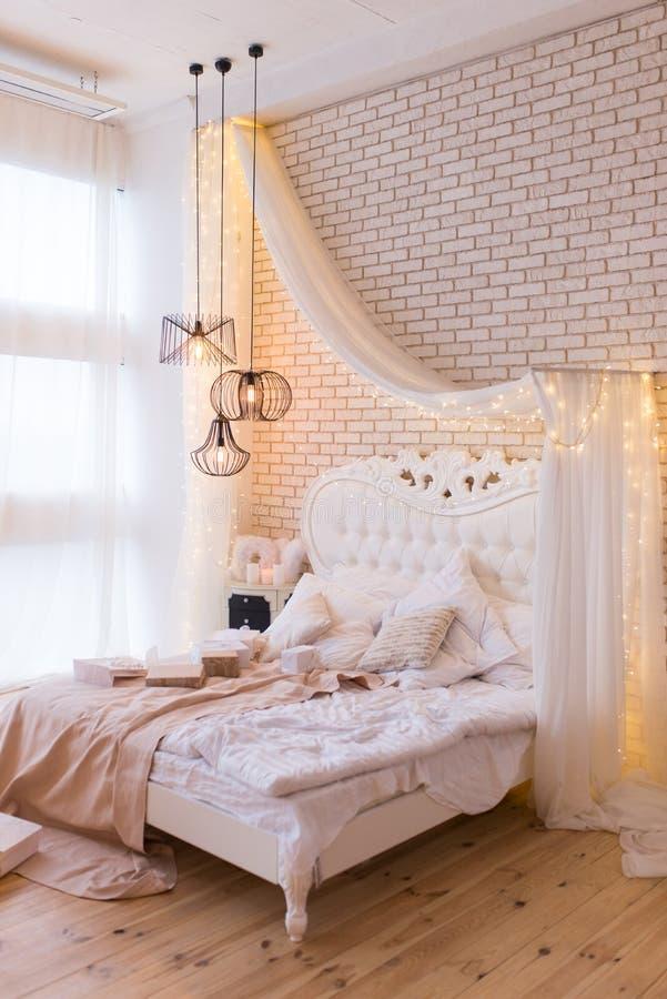 Groot comfortabel dubbel koninklijk bed in elegant klassiek binnenland tegen een geweven witte bakstenen muur stock foto
