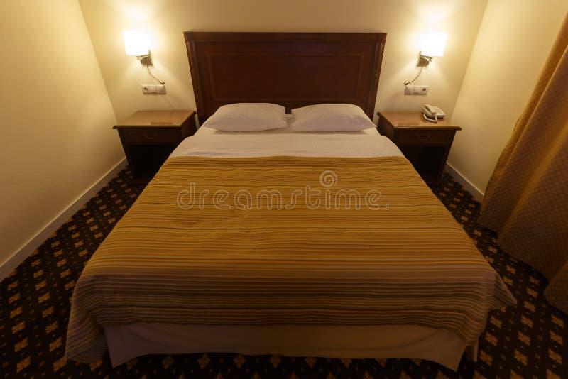 Groot comfortabel tweepersoonsbed in een kleine hotelruimte royalty-vrije stock foto
