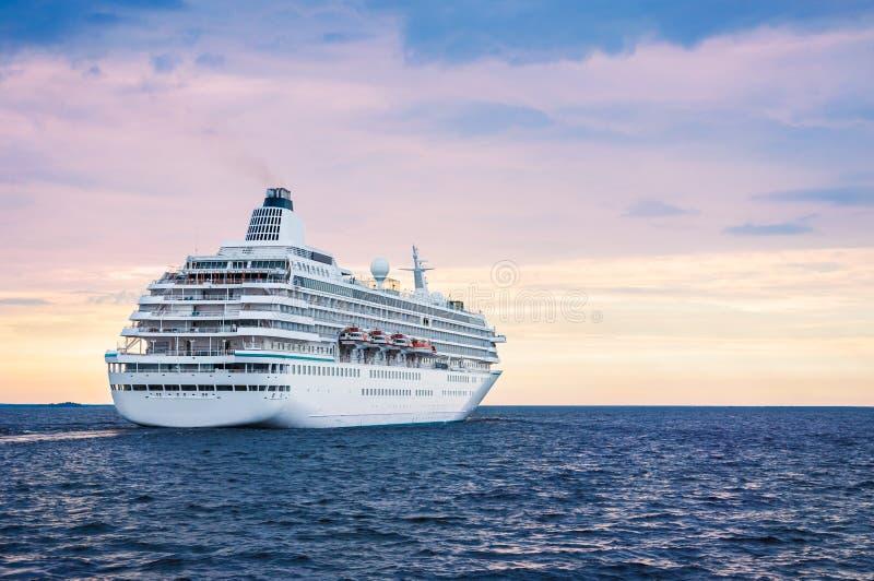 Groot cruiseschip in het overzees bij zonsondergang stock afbeeldingen