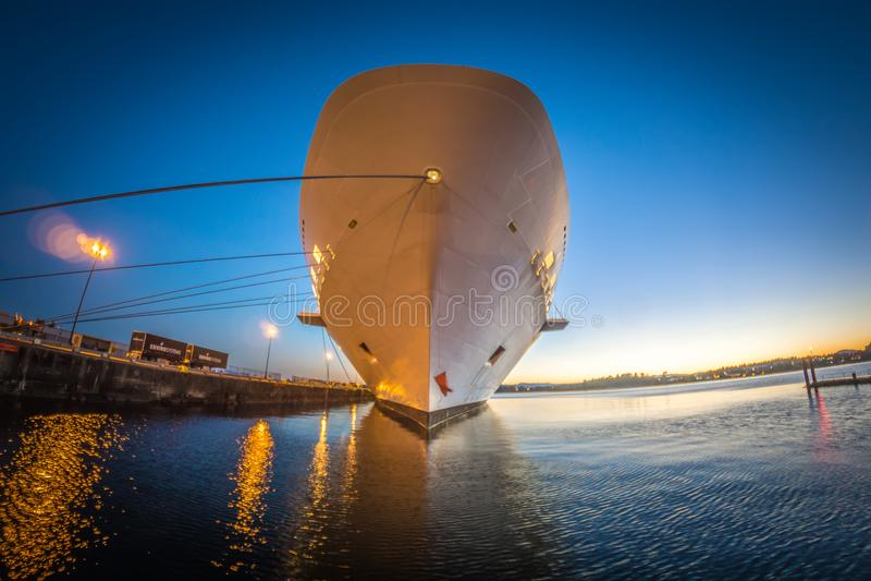 Groot die cruiseschip bij pijler bij zonsondergang wordt vastgelegd stock foto