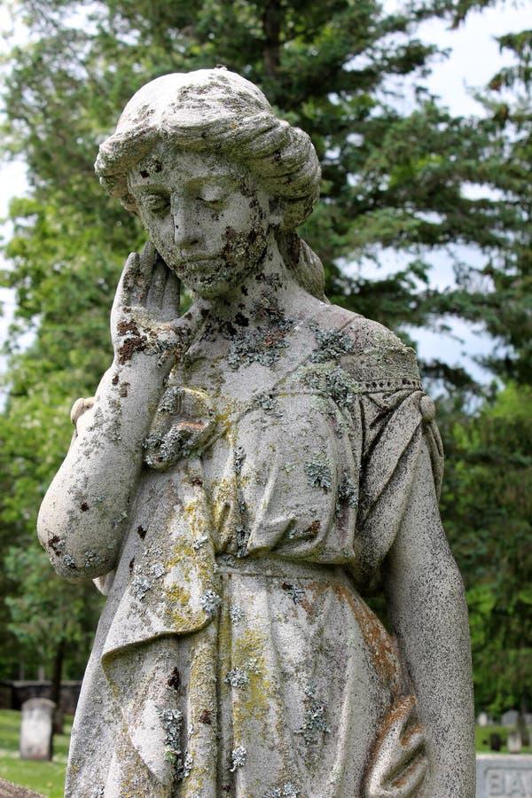 Groot die steenbeeldhouwwerk van het huilen engel in mos in begraafplaats wordt behandeld stock foto