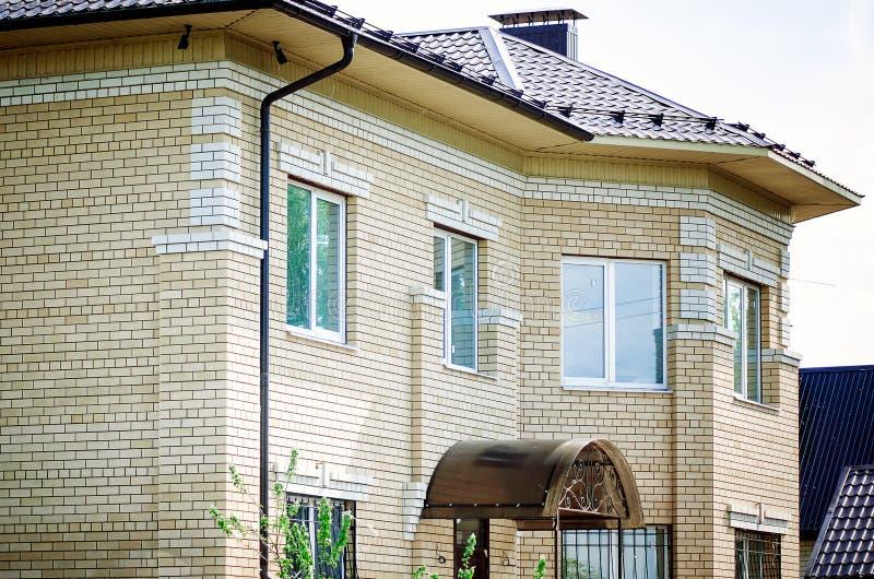 Groot die two-storey plattelandshuisje van witte baksteen wordt gemaakt stock foto