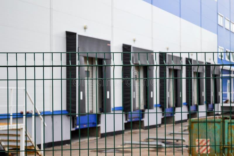 Groot distributiepakhuis op de achtergrond achter een van tralies voorzien omheining stock afbeeldingen